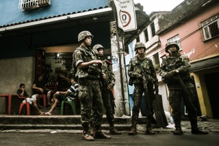 Residents carry on with their lives as soldiers patrol the streets of Maré favela complex, in Rio. Image courtesy Midia NINJA